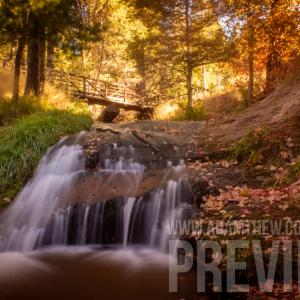 Waterfall Rushes Under Bridge On An Autumn Morning
