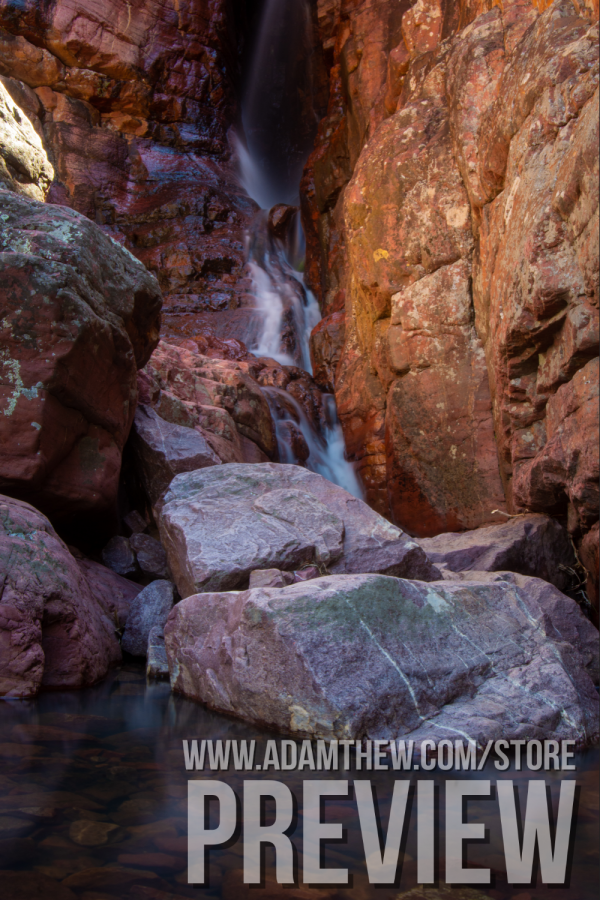 Waterfall Pours From Red Rocks